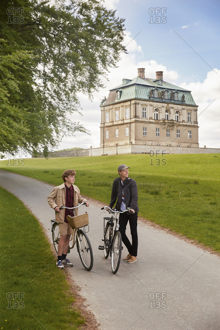 Denmark - June 17, 2014: Two young men with bicycles in front of the Hermitage Palace outside Copenhagen, Denmark