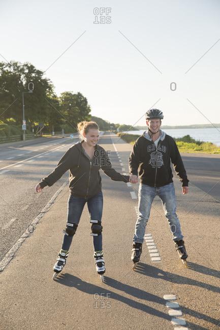 Denmark - June 17, 2014: A young couple on rollerblades in Strandvejen outside Copenhagen, Denmark