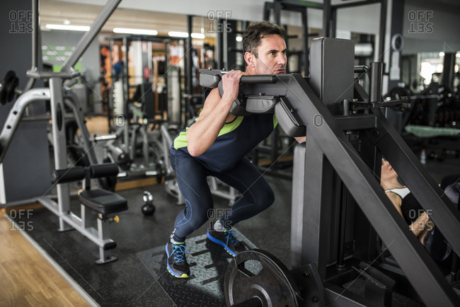 Senior man traning quadriceps and femoral muscle in gym