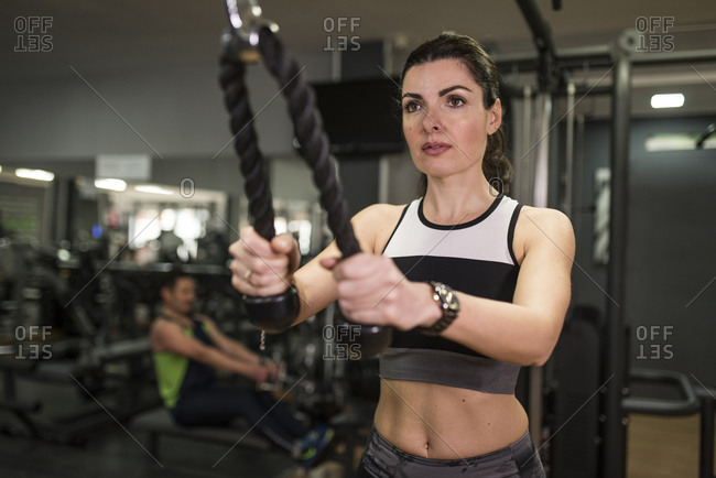 Mature woman training triceps muscle in gym