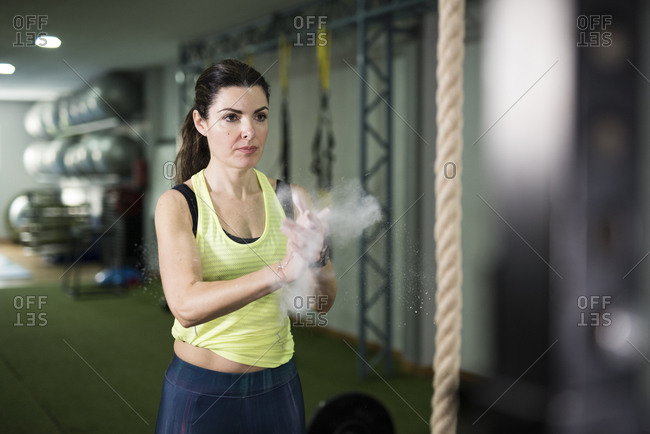 Woman putting weightlifting chalk on hands at the gym