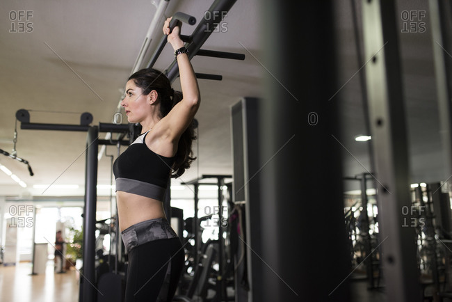 Mature woman exercising chin ups in gym