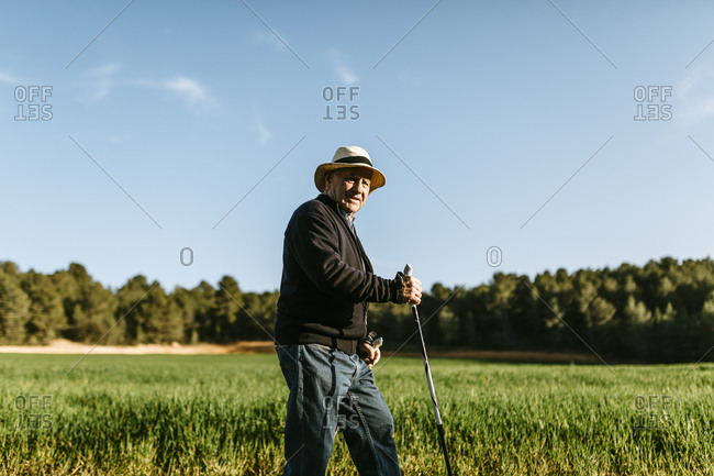 Senior man walking in a field using sticks