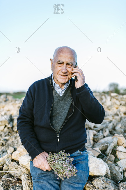 Senior man using a phone outdoors