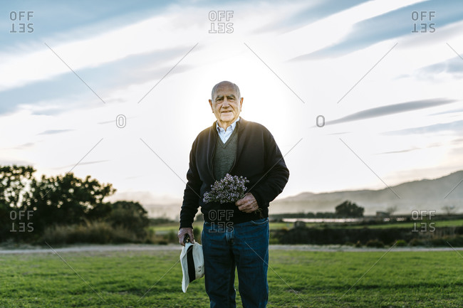Senior man with bouquet of flowers standing in a field