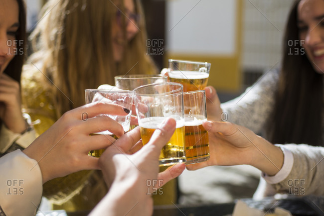 Friends toasting with beer glasses in a street cafe