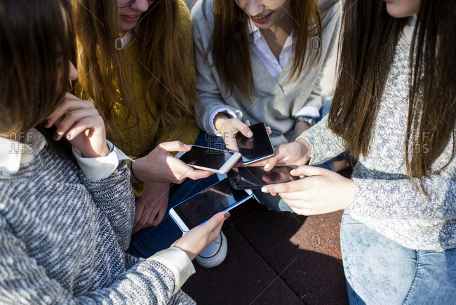 Four young women comparing her smartphones