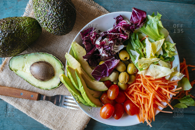Salad with avocado, tomatoes, carrot, olives and lettuce
