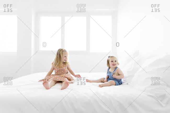 Two happy little sisters sitting on a white bed