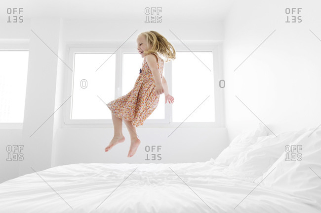 Laughing little girl wearing summer dress jumping on a white bed