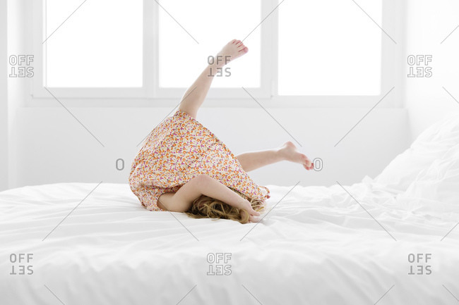 Little girl wearing a dress doing somersault on bed