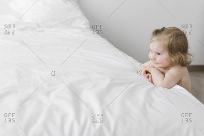 Smiling toddler girl leaning on white bed