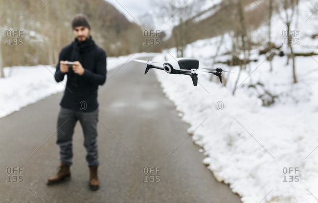 Man navigating a drone in the snowy mountains