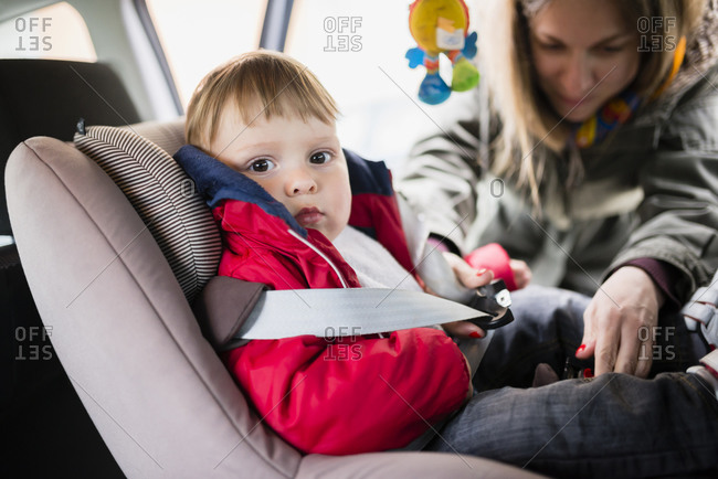 Woman fastening seat belt of his little son sitting in child's seat in a car