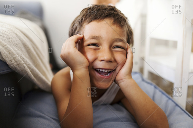 Portrait of laughing little boy with head in his hands