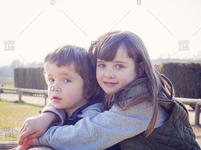 Portrait of smiling girl hugging her little brother