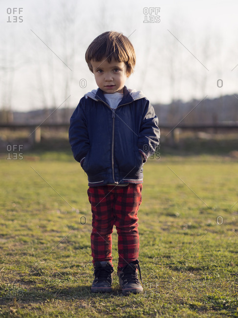 Little boy standing on grass with hands in pockets