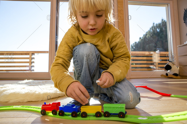 Little boy playing with toy train at home