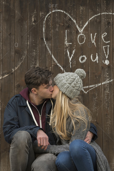 Young couple kissing with a drawn heart and love you written on a wooden wall, Munich, Bavaria, Germany