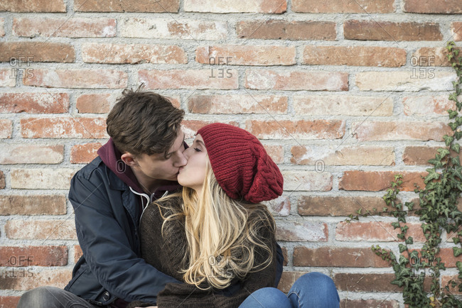 Young couple kissing against brick wall, Munich, Bavaria, Germany