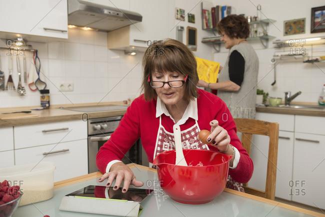 Senior woman seeking recipe on digital tablet for cake, Munich, Bavaria, Germany