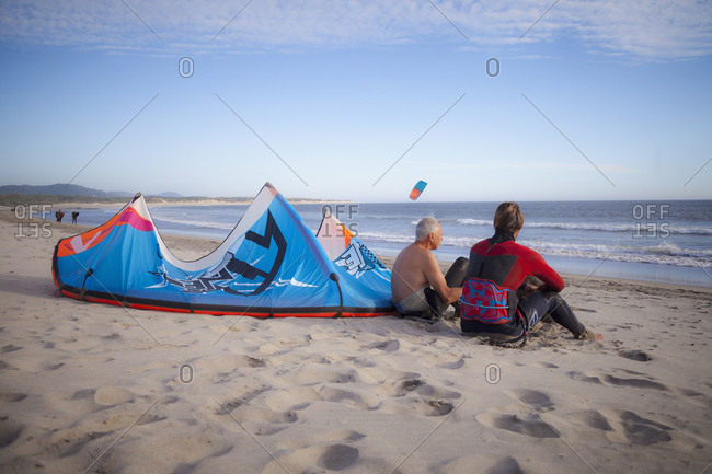 Kite surfer with his father sitting on the beach, Viana do Castelo, Norte Region, Portugal