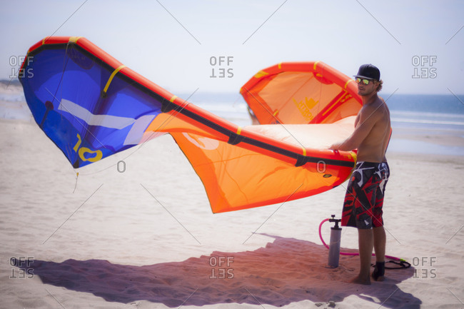 Young man with kiteboard standing on beach, Viana do Castelo, Norte Region, Portugal