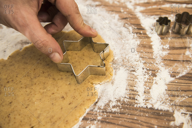 Close up of a man cutting out star shape cookies, Munich, Bavaria, Germany