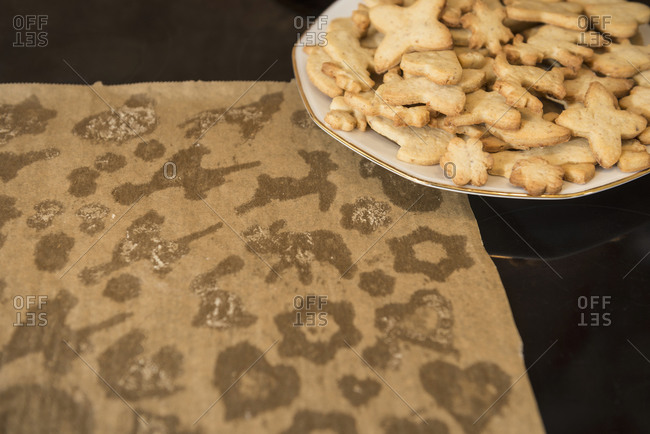 Used baking paper with different shaped cookies in plate, Munich, Bavaria, Germany