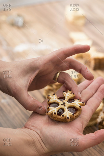 Close up of a woman holding snowflake shaped cookies with marmalade, Munich, Bavaria, Germany
