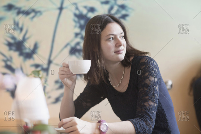 Young woman drinking coffee in coffee shop, Freiburg Im Breisgau, Baden-Wurttemberg, Germany
