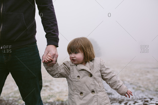 Girl in trench coat holding man's hand