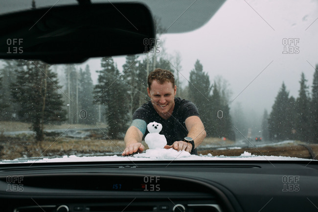 Man building snowman on car