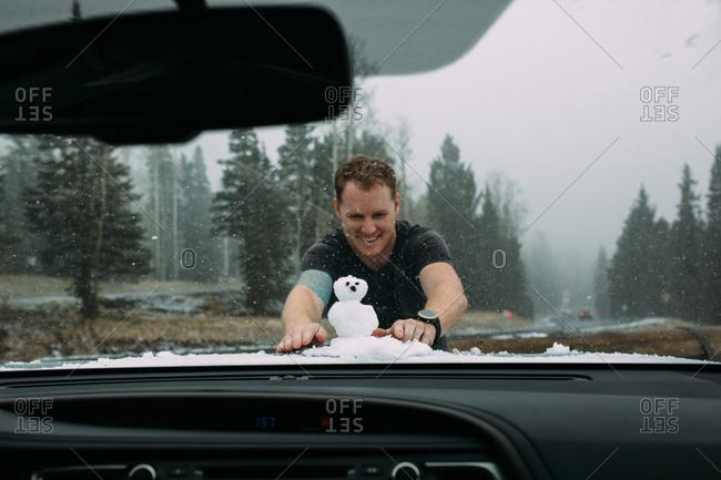Man building snowman on car