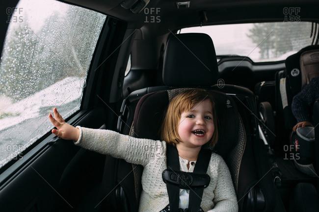 Laughing girl in car in winter