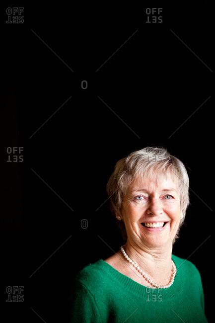 Close-up portrait of smiling senior woman against black background