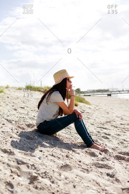 Woman smoking cigarette while sitting on sand at beach