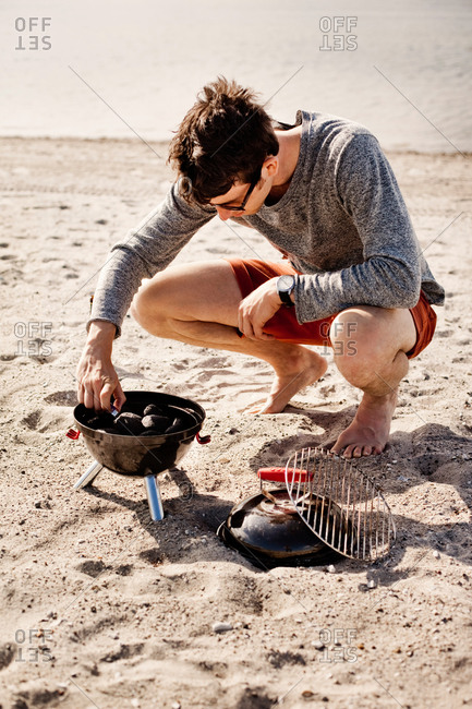 Young man igniting barbecue at the beach
