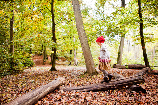 Full length of girl walking on log in forest