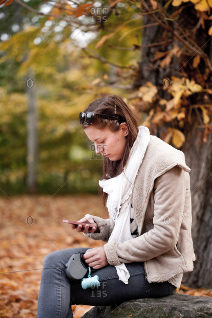 Side view of young woman reading text message on smart phone in forest