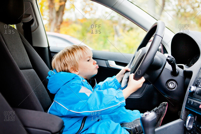 Full length side view of boy holding car's steering wheel