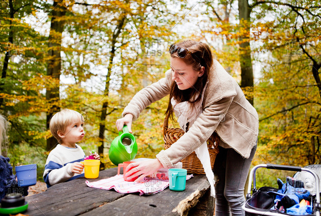 Mother pouring drink for son in picnic at forest
