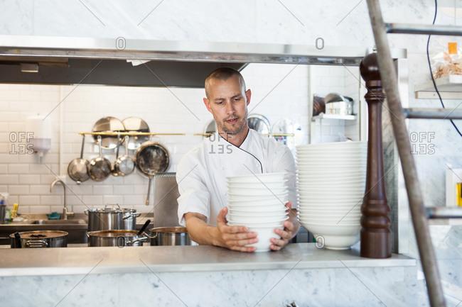 Chef arranging bowls in restaurant kitchen