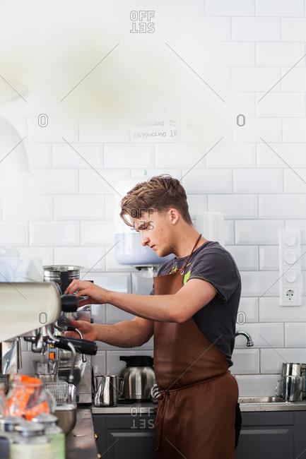 Barista making coffee using espresso machine at restaurant