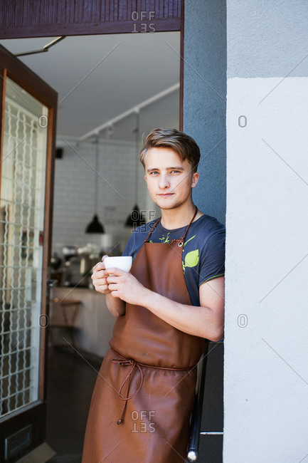 Portrait of barista leaning on wall while holding coffee outside commercial kitchen