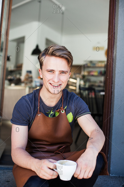 Portrait of happy barista holding coffee while sitting on steps outside restaurant