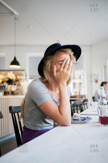 Young woman covering face with hand while sitting at restaurant table