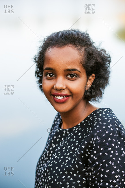 Portrait of smiling young woman against lake