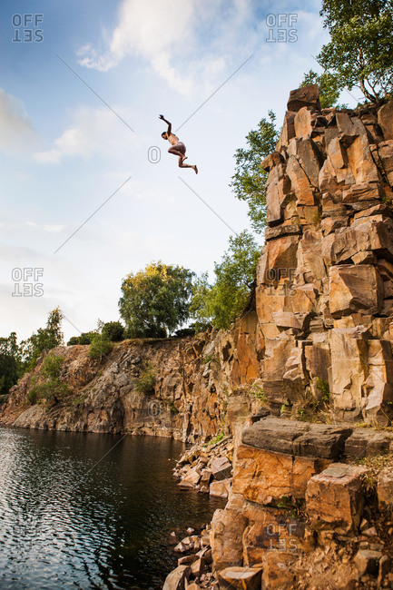 Low angle view of man jumping from cliff into lake