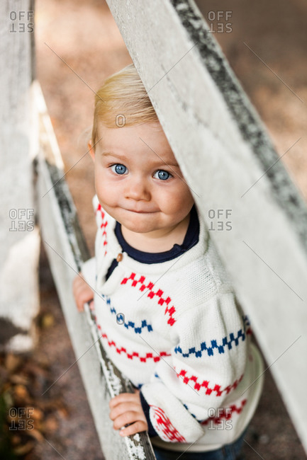High angle portrait of baby girl standing by wooden fence in park